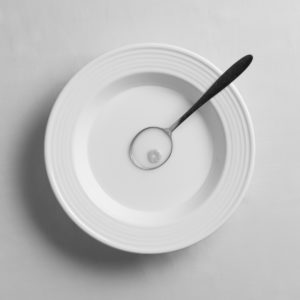One circular piece of breakfast cereal in a spoon with milk in a white bowl on a white background